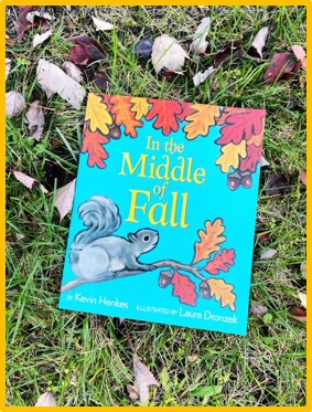 "The cover of the book ""In the Middle of Fall"" is shown. The book is laying in the grass with leaves around it."