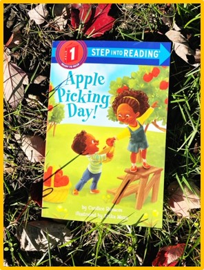 "The cover of the book ""Apple Picking Day"" is shown. The cover shows a girl standing on a ladder getting an apple from the tree and a little boy standing next to her on the grass. The book is laying in the grass, with leaves surrounding it."
