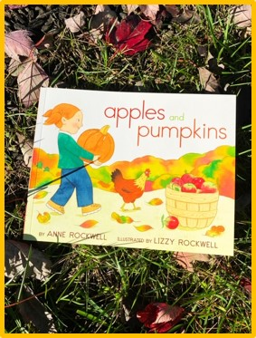 "The cover of the book ""Apples and Pumpkins"" is shown. The cover has a girl walking on a farm, holding a pumpkin. Also on the cover is a bushel of apples and a chicken. The book is laying in the grass with leaves surrounding it."