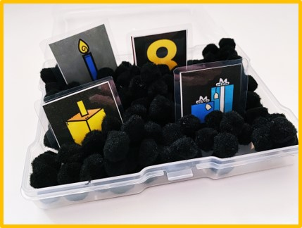 In this image, I am sharing one of my three cortical visual impairment Christmas activities. A small container with black pom poms is shown. There are 4 picture cards in the bin: candle, the number eight, a dreidel, and presents.