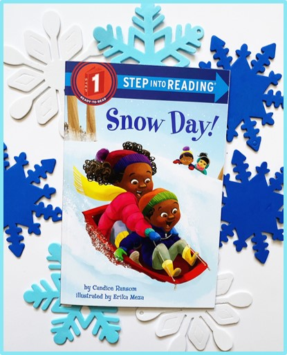 """This image shows the front of the book """"Snow Day!"""". Behind the picture book are white and blue foam snowflakes."""