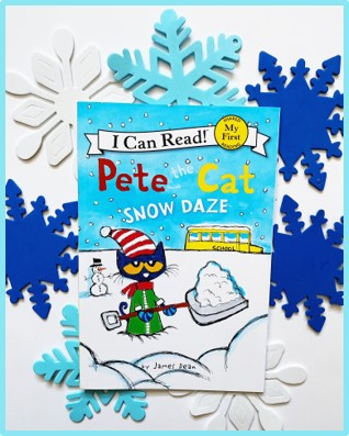 """This image shows the front of the book """"Pete the Cat: Snow Daze"""". Behind the picture book are white and blue foam snowflakes."""