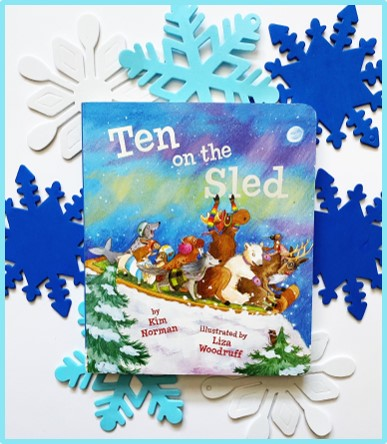 """This image shows the front of the book """"Ten on the Sled"""". Behind the picture book are white and blue foam snowflakes."""