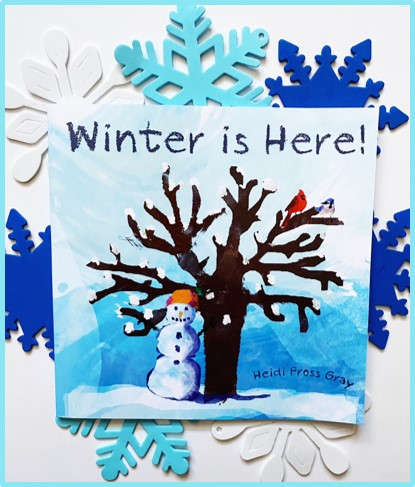 """This image shows the front of the book """"Winter is Here."""" Behind the picture book are white and blue foam snowflakes."""