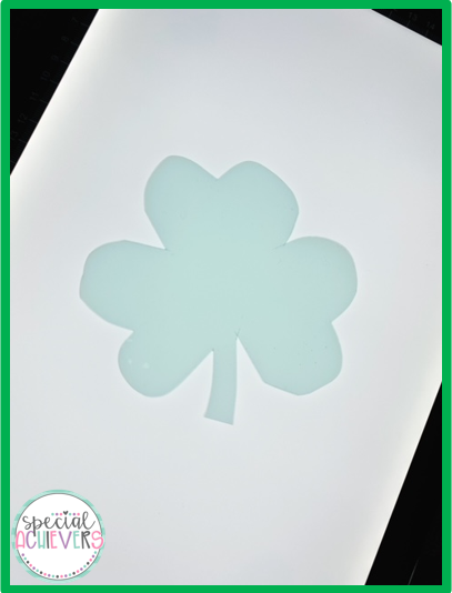 This image shows a green translucent shamrock on a light box.