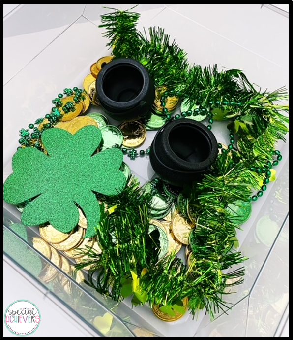 This image shows an St. Patrick's Day activity, specifically a sensory bin. In the bin is green beads, gold coins, mini cauldrons, and glitter shamrocks.