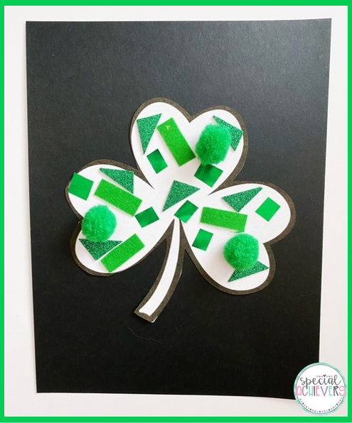 A white shamrock is on a black piece of paper. The shamrock is decorated with a variety of green textures including: green pom poms, green felt, green glitter foam paper, and green metallic paper.