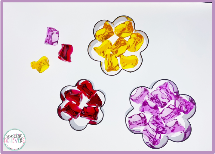 Three flower shaped cookie cutters are shown on a light table. In each of the cookie cutters are translucent gems of the following colors: yellow, red, and purple.