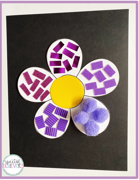 A white flower is on a black piece of paper. The flower is decorated with a variety of purple textures including: purple pom poms, purple felt, purple corrugated paper, purple glitter foam paper, and purple metallic paper.