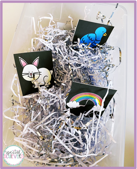 A CVI-friendly spring sensory bin is shown. The bin is a clear plastic container. In the container is white and silver shredded paper and CVI-friendly spring vocabulary cards including a bird, bunny and rainbow.