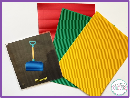 """The image shows a page from a winter adapted book. The page shows a blue shovel, made from corrugated paper, with the word """"shovel"""" written below. Next to the page is red, green, and yellow corrugated paper."""