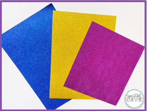 Three pieces of glitter foam paper are pictured. From left to right, the colors are blue, yellow, and pink.