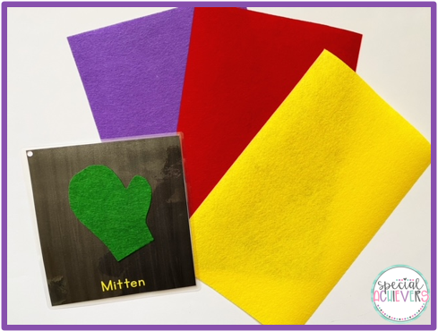 """The image shows a page from a winter adapted book. The page shows a green felt mitten with the word """"mitten"""" written below. Next to the page is purple, red, and yellow felt."""