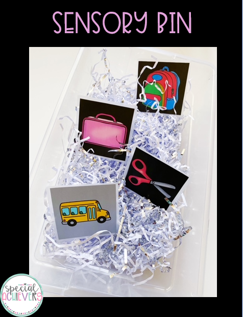 """The text at the top says """"Sensory Bin."""" Below the text is an image of a clear bin, with white and silver shredded paper inside, with 4 vocab cards: bus, lunchbox, scissors, and backpack."""