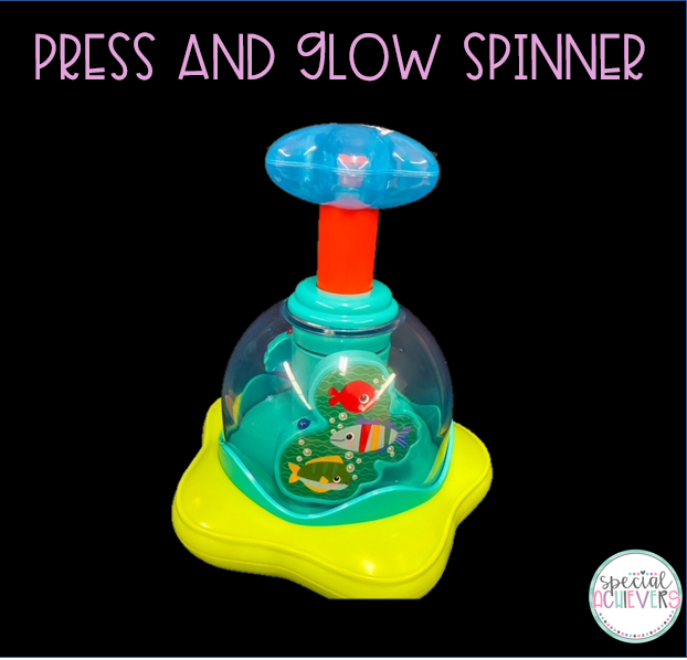 """The text at the top of the image says """"Press and Glow Spinner."""" Below fish themed toy that is activated by pushing the large button on the top. When this is pushed the base spins and lights up."""