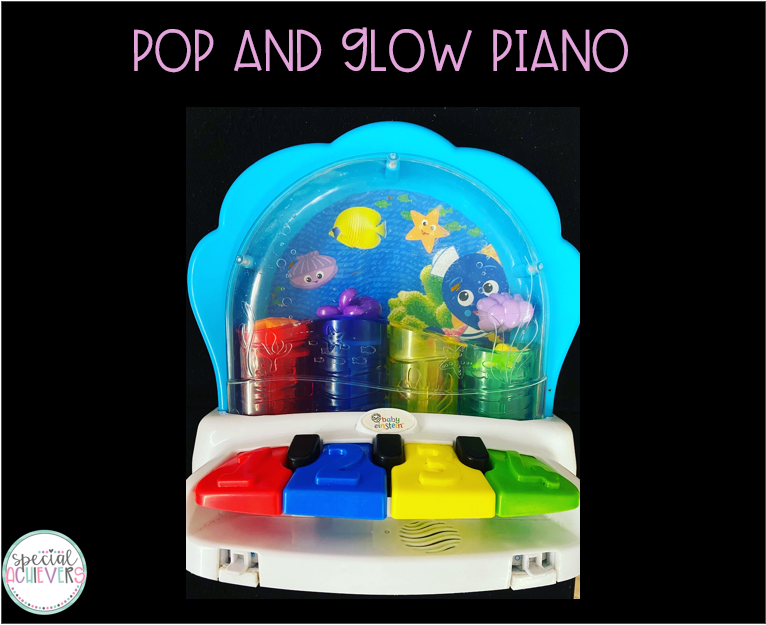 """The top of the image says """"Pop and Glow Piano."""" The image shows a blue ocean themed piano. There are four piano keys that are red, blue, yellow and green. Each key is connected to a colorful tube in the back part of the piano that pops up fish when played."""