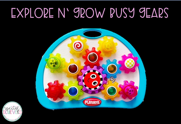 """The text at the top of the image says """"Explore N' Grow Busy Gears."""" The image shows the white toy base with multicolored interlocking translucent gears on top."""